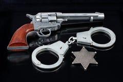 Handschellen, Stern und Revolver Stockfotografie