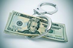 Handschellen und Dollarscheine Stockfotografie