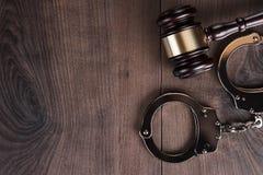 Handschellen und Richterhammer auf hölzernem Hintergrund Stockbild