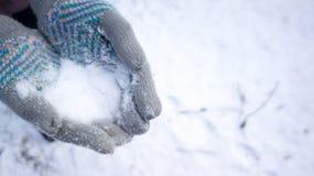 Handschoenen die sneeuw in sneeuw houden royalty-vrije stock afbeelding