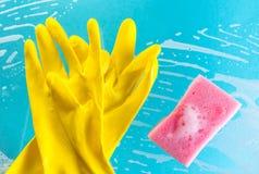 Handschoenen en spons in schuim op een blauwe achtergrond Royalty-vrije Stock Foto's