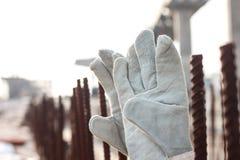 handschoenen en staalbars op concrete achtergrond Stock Afbeeldingen