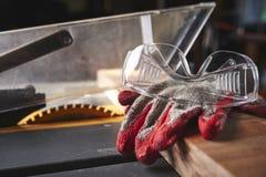Handschoenen en veiligheidsbril op een lijstzaag Stock Afbeelding