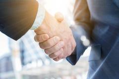 Handschok van zakenman twee met zongloed, bedrijfsconceptua Stock Fotografie