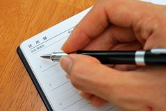 Handschreiben mit Feder auf japanischem Adressbuch Stockfotos