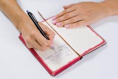 Handschrift im offenen Notizbuch auf Tabelle Stockbild