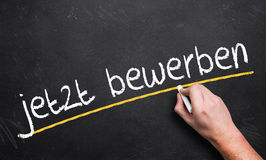 Handschrift ` treffen jetzt zu! ` auf einer Tafel auf Deutsch Lizenzfreie Stockbilder