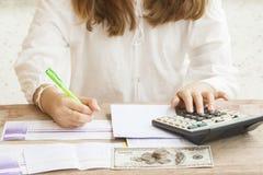 Handschriftrechnungsablagerung bei Sparbuchbank für Finanzierungskosten und Einkommen Stockfotografie