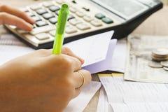 Handschriftrechnungsablagerung bei Sparbuchbank für Finanzierungskosten und Einkommen Stockbild