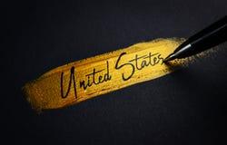 Handschrifts-Text Vereinigter Staaten auf goldenem Pinsel-Anschlag stockfotografie