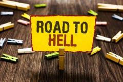 Handschriftstext-Schreiben Straße zur Hölle Konzept, das Wäscheklammerholding Reise des extrem gefährlichen Durchgangs dunkle ris stockbild