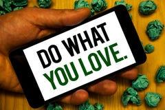 Handschriftstext tun, was Sie lieben Konzept, das positive auserlesene Hand Desire Happiness Interest Pleasure Happys hält Telefo lizenzfreie stockbilder