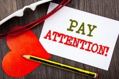 Handschriftstextvertretung Lohn-Aufmerksamkeit Geschäftskonzept für gibt aufpassen die aufmerksame Warnung acht, die auf klebrige stockbild