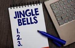 Handschrifttekst Jingle Bells Concept die beroemdste traditionele Open het notitieboekje witte pagina betekenen van het Kerstmisl stock foto's