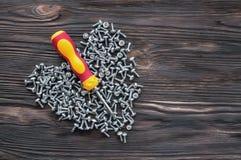 Handschroevedraaierschroeven en pennen op een houten achtergrond royalty-vrije stock foto