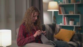 Handschuß der Frau sitzend auf Sofa und nachts strickend stock video