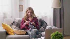 Handschuß der Frau sitzend auf Sofa und strickender Häkelarbeitkleidung im gemütlichen Haus stock footage