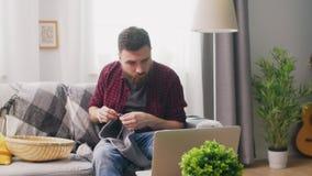 Handschuß des Mannes sitzend auf Sofa und das Stricken lernend stock video footage
