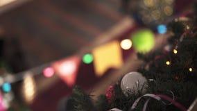Handschuß des Tannenbaums und der Lichter und der Lampen der unterschiedlichen Farbe mit bokeh Effekt zuhause stock video