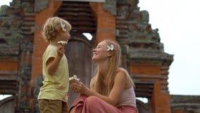 Handschuß einer jungen Frau und ihres Sohns, die auf der Treppe des Tempels Taman Ayun auf der Bali-Insel sitzen stock footage