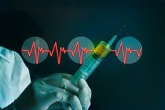 Handschuh der Spritze in der Hand einer Herzfrequenz auf dem blauen Labor medizinisch Lizenzfreies Stockbild
