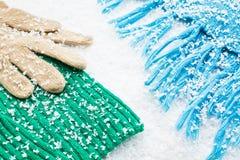 Handschuhe und Schals der Wollen über dem Schnee stockbild
