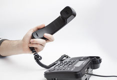 With handset arm. Hand on a white background with black handset Royalty Free Stock Image