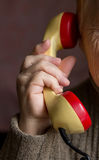 The handset is in the hand of an old woman. Royalty Free Stock Photo