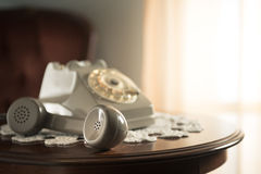 Handset on hold. Vintage telephone on doily and round wooden table with handset on hold Stock Photos