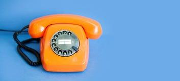 Handset orange färg för den Retro telefonen, tappning mottagaren på blå bakgrund kopiera avstånd arkivfoto