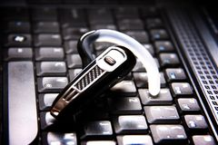 Handsfree bluetoothhoofdtelefoon en laptop Royalty-vrije Stock Afbeelding
