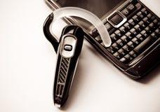 Handsfree bluetoothhoofdtelefoon en mobiele telefoon Stock Foto