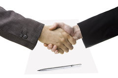 Handshake. Business handshake on paper and pen on white royalty free stock photos