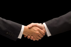 Handshake. Executives handshake against a black background Stock Photography