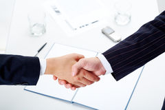 Handshake. Woman and man shaking hands over paper, pen, phone, glasses royalty free stock photos