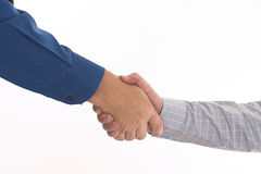 Handshake. Two businessmen in blue shirts shake hands over white Stock Images