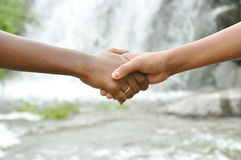Handshake. Detail of two hands shaking in front of water falls Royalty Free Stock Images