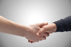Handshake. Two female hands of different ages holding each other in a handshake. Copy space on top Stock Photos
