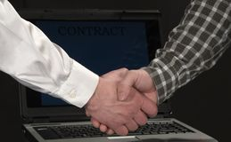 Handshake. Business men shaking hands in front of a laptop after a successful contract Royalty Free Stock Image
