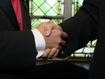 Handshake. Detail of men dressed in formal attire shaking hands Stock Image