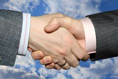Handshake. Hand shake on a background of the blue sky Stock Photos