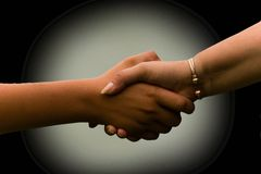 Handshake. Two people shaking hands, one adult female and her young son Royalty Free Stock Photo