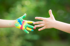Handshake. With painted hands against green spring background stock photos