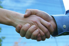 Handshake. Close up handshake with blue office building in background Royalty Free Stock Photo