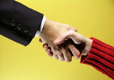 Handshake. Agreement on a yellow background. May fit a CEO to employee or business to end user concept royalty free stock photo