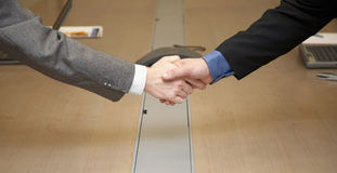 Handshake. In conference room, computers and conference phone in the background Stock Photography