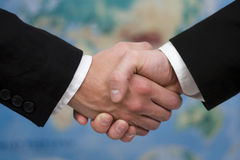 Handshake. Two guys handshake on map as background Stock Images