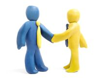 Handshake. Two plasticine businessmen shake their hands isolated on white royalty free stock photography