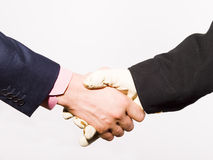 Handshake. Two hands shown in a handshake.  One of a businessman the other wearing a latex glove.  Isolated against a white background Royalty Free Stock Photography