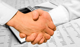 Handshake. Over paper and pen,blurry computer in the background Stock Image